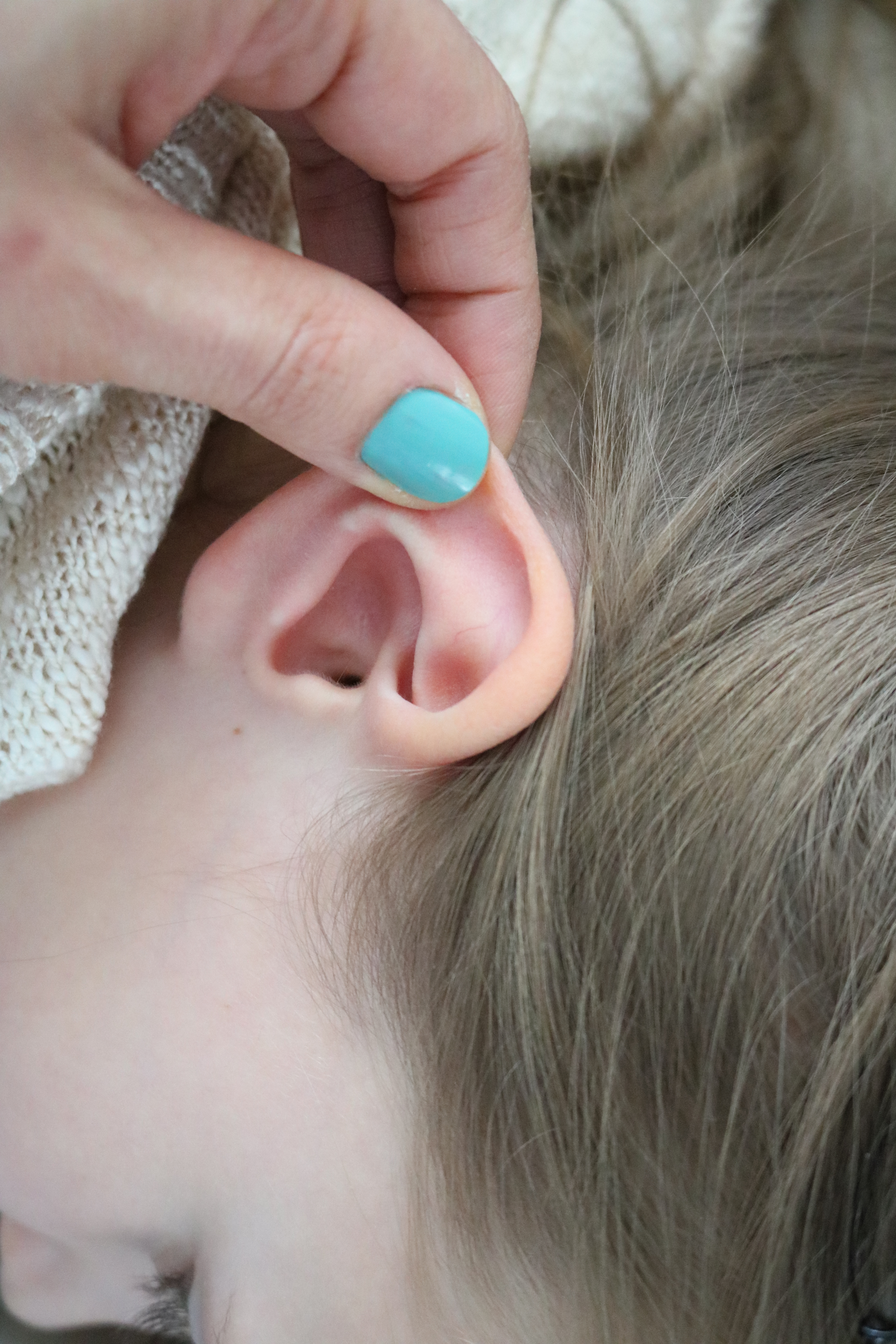 Gently pulling on the ear to check for earache and/or ear infection in infants and babies